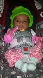 newborn baby strapped into a carseat, while wearing a bright green hat, pink onesie, and pink polka dot mittens